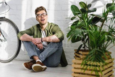 Photo pour Bel homme en chemise verte, jeans et lunettes souriant et assis sur le sol près du mur de briques, vélo et plantes dans le bureau - image libre de droit