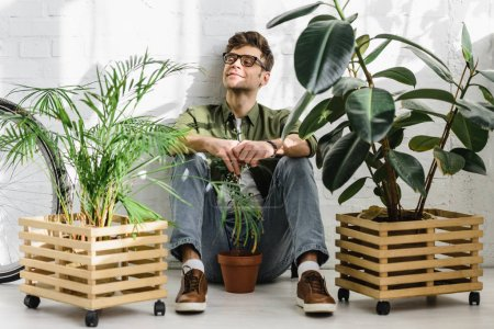 Photo for Happiness man in shirt and glasses sitting near pots with plants and brick wall in office - Royalty Free Image