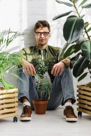 Foto de Hombre en camiseta y gafas sentado cerca de macetas con plantas y pared de ladrillo en oficina - Imagen libre de derechos
