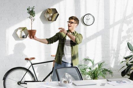 Photo pour Homme beau délicat en chemise verte et jeans tenant pot avec plante au bureau - image libre de droit