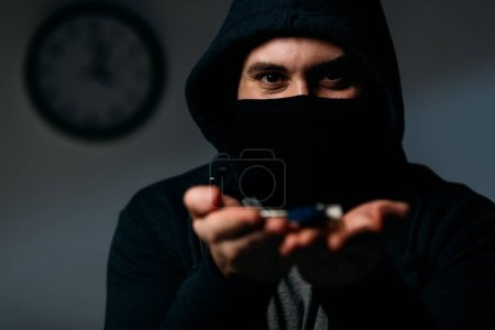 Photo pour Criminel dans la capuche et le masque montrant les clés à la caméra - image libre de droit