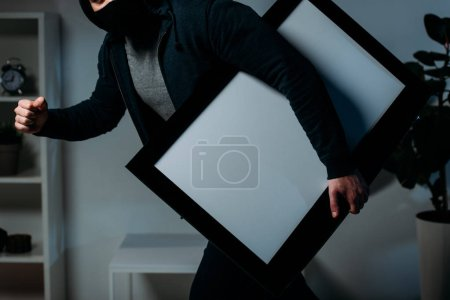 Photo for Partial view of thief stealing flat-screen tv with blank screen - Royalty Free Image