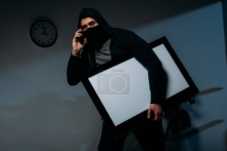 Photo for Thief in mask talking on smartphone while stealing flat-screen tv with blank screen - Royalty Free Image