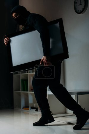 Photo for Cautious thief in mask stealing flat-screen tv with blank screen - Royalty Free Image