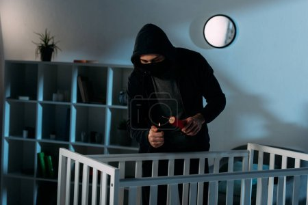 Photo for Criminal in mask igniting dynamite near crib in dark room - Royalty Free Image