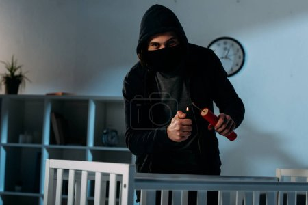 Photo for Criminal in mask igniting dynamite near crib and looking at camera - Royalty Free Image