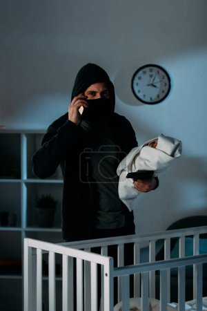 Photo for Kidnapper in mask holding infant child and talking on smartphone - Royalty Free Image