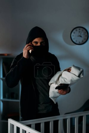 Photo for Kidnapper with gun holding infant child and talking on smartphone - Royalty Free Image