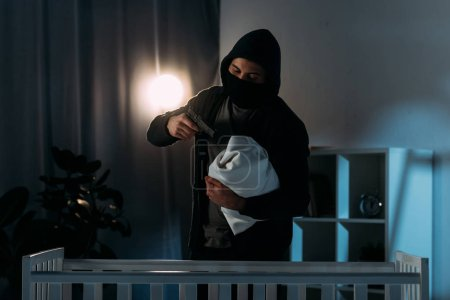 Photo for Kidnapper in mask aiming gun at infant child in dark room - Royalty Free Image
