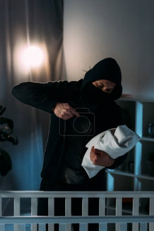 Photo for Kidnapper in black clothes aiming gun at infant child - Royalty Free Image