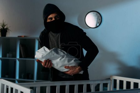 Photo for Kidnapper in black mask holding infant child near crib - Royalty Free Image