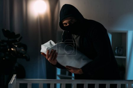 Photo for Kidnapper in mask and hoodie holding infant child in dark room - Royalty Free Image