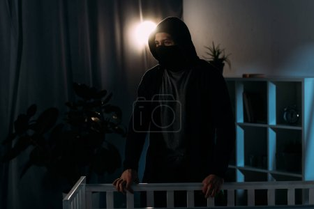 Photo for Pensive kidnapper in mask standing near crib and looking away - Royalty Free Image