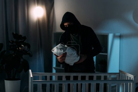 Photo for Kidnapper in mask and hoodie holding infant child while standing near crib - Royalty Free Image