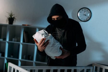 Photo for Kidnapper in mask and black hoodie standing near crib and holding infant child - Royalty Free Image