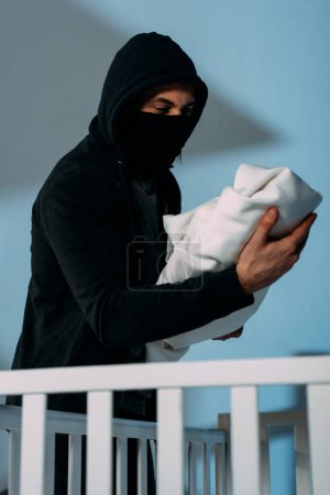 Photo for Kidnapper in mask standing beside crib and holding infant child - Royalty Free Image