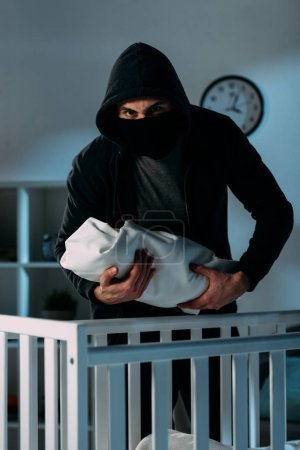 Photo for Kidnapper in black clothes and mask holding infant child - Royalty Free Image