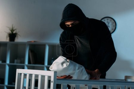 Photo for Kidnapper in mask and hoodie standing near crib and holding infant child - Royalty Free Image