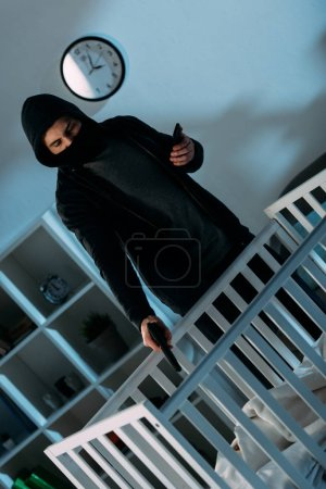 Photo for Criminal in mask and hoodie aiming gun at infant child in crib - Royalty Free Image
