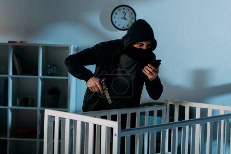 Photo pour Criminel en colère parlant sur smartphone et visant pistolet dans la crèche - image libre de droit