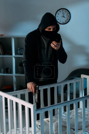 Photo for Criminal in mask talking on smartphone and aiming gun in crib - Royalty Free Image