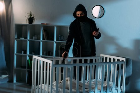 Photo for Criminal in mask holding smartphone and aiming gun in crib - Royalty Free Image