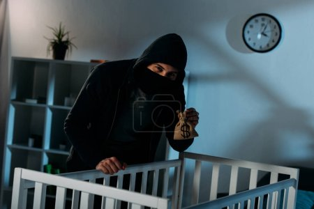 Photo for Kidnapper standing near crib with money bag and looking at camera - Royalty Free Image