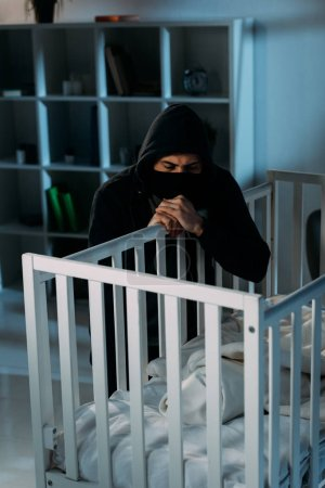 Photo for Serious kidnapper in black mask looking in crib in dark room - Royalty Free Image