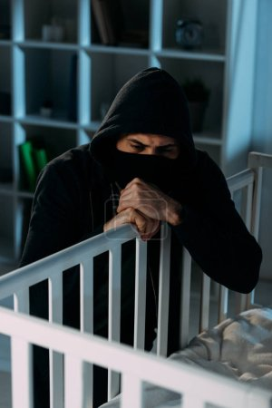Photo for Pensive kidnapper in black mask looking in crib in dark room - Royalty Free Image