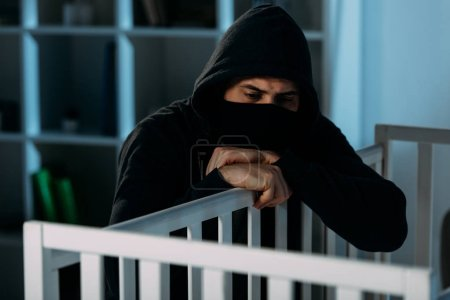 Photo for Sad kidnapper in mask and hoodie looking in crib - Royalty Free Image
