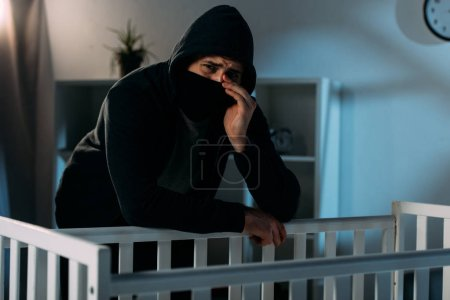 Photo for Crying kidnapper in mask standing near crib in dark room - Royalty Free Image