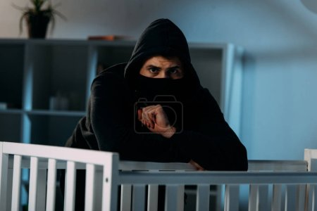 Photo for Worried kidnapper in black clothes and mask standing beside crib - Royalty Free Image