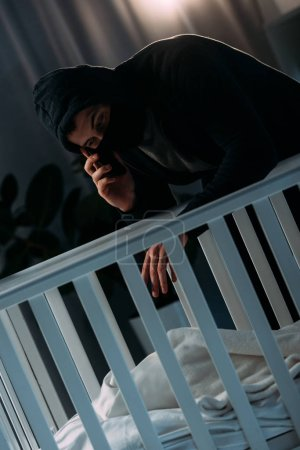 Photo for Kidnapper in mask talking on smartphone while standing near crib - Royalty Free Image