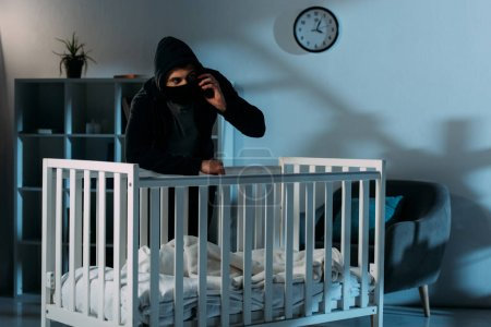 Photo for Kidnapper in black mask standing near crib and talking on smartphone - Royalty Free Image