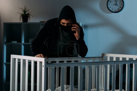 Photo for Kidnapper in mask talking on smartphone and looking in crib - Royalty Free Image