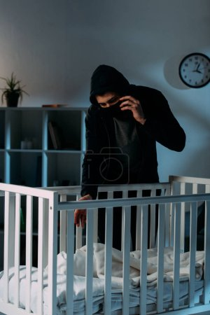 Photo for Criminal in mask talking on smartphone while kidnapping child - Royalty Free Image