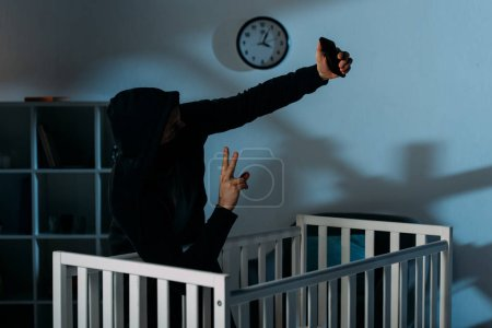 Photo for Kidnapper taking selfie near crib and showing peace sign - Royalty Free Image
