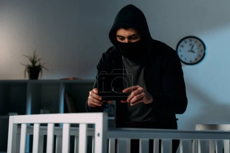 Photo for Criminal in mask standing near crib and taking photo - Royalty Free Image