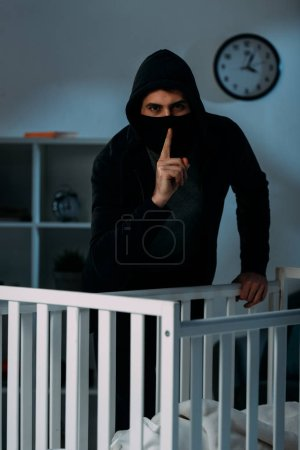 Photo for Kidnapper in mask standing near crib and showing hush sign - Royalty Free Image