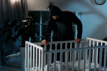 Photo for Kidnapper in mask and hoodie looking in crib in dark room - Royalty Free Image