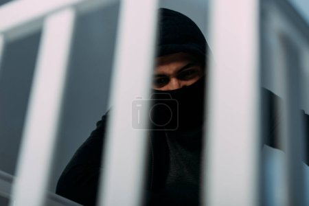 Photo for Angry criminal in black clothes and mask looking down - Royalty Free Image