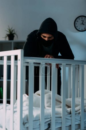 Photo for Pensive kidnapper standing in dark room and looking in crib - Royalty Free Image