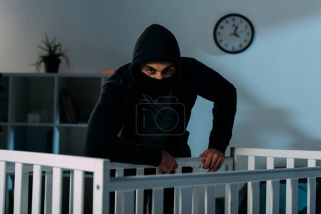 Photo for Angry kidnapper in black mask standing near crib and looking at camera - Royalty Free Image