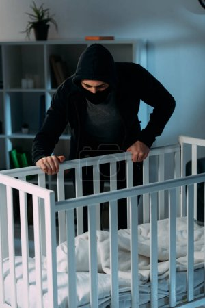 Photo for Criminal in mask standing near crib and looking at baby - Royalty Free Image