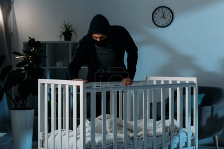 Photo for Kidnapper in black clothes standing in dark room and looking in crib - Royalty Free Image