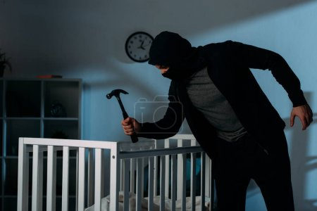Photo for Criminal in mask holding hammer while standing near crib in dark room - Royalty Free Image