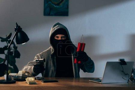 Photo pour Terroriste en colère masqué tenant une arme et de la dynamite alors qu'il était assis au bureau dans une pièce sombre - image libre de droit