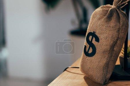 Photo pour Sac d'argent avec signe dollar debout sur une table en bois - image libre de droit