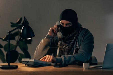 Photo pour Criminel grave au masque noir, parler au téléphone dans la chambre - image libre de droit