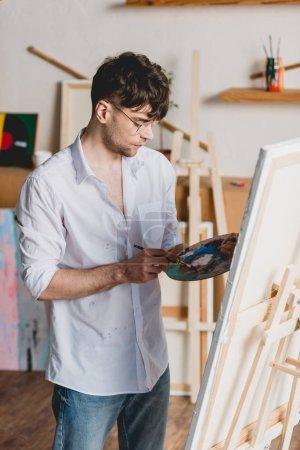 Foto de Hermoso artista mezcla pinturas paleta estando cerca de caballete con lienzo - Imagen libre de derechos